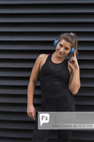 Porträt einer lächelnden jungen Frau  die mit schnurlosen Kopfhörern Musik hört