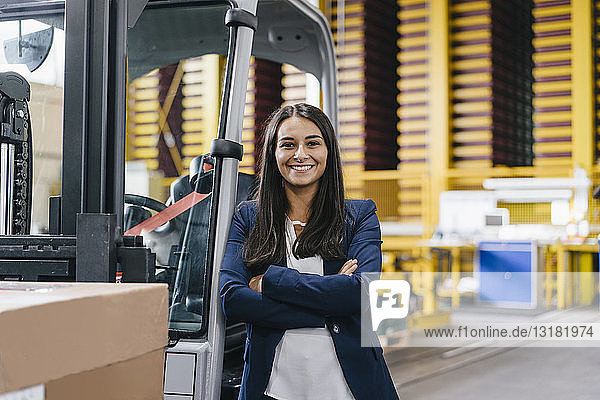 Confident woman standing in logistics center  with arms crossed