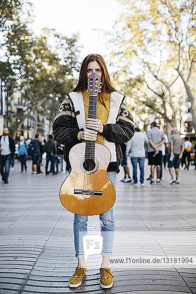 Rothaarige Frau mit Gitarre in der Hand in der Stadt