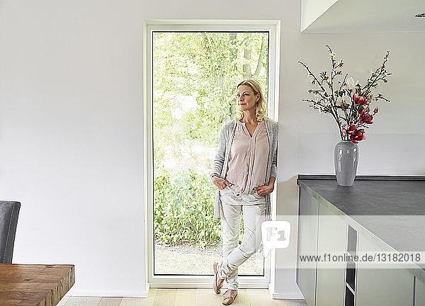 Frau steht zu Hause vor französischer Tür