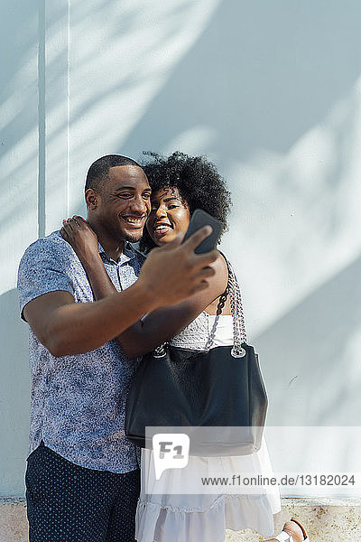 Smiling young couple embracing and taking a selfie