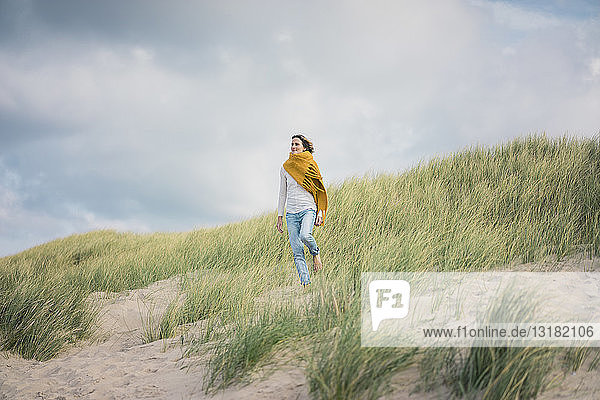 Reife Frau entspannt sich in den Dünen und genießt den Wind