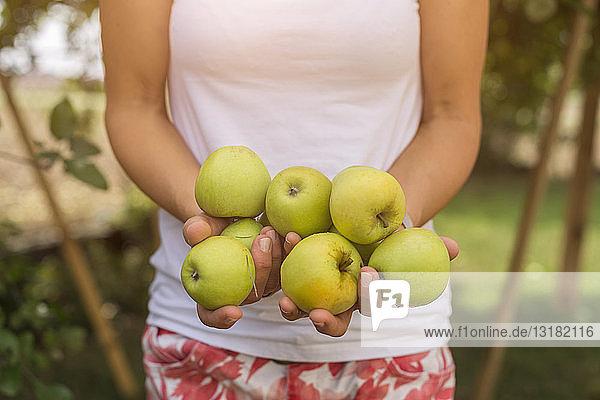 Frau mit geernteten Äpfeln