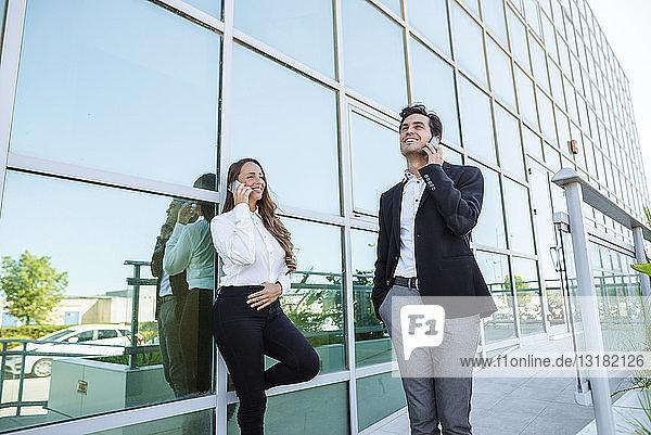 Lächelnde Geschäftsfrau und Geschäftsmann am Handy vor dem Bürogebäude