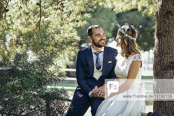 Happy bridal couple holding hands in a park