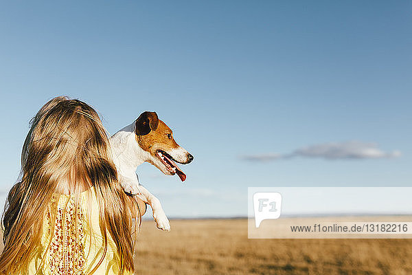 Mädchen hält Hund auf einem Feld