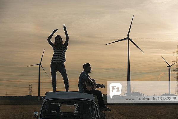 Glückliches Paar mit Gitarre auf dem Dach eines Wohnmobils in ländlicher Landschaft in der Abenddämmerung
