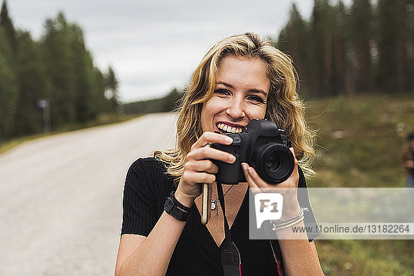 Finland  Lapland  portrait of happy young woman holding camera at country road