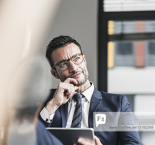 Businessman using digital tablet  sitting in office with feet up