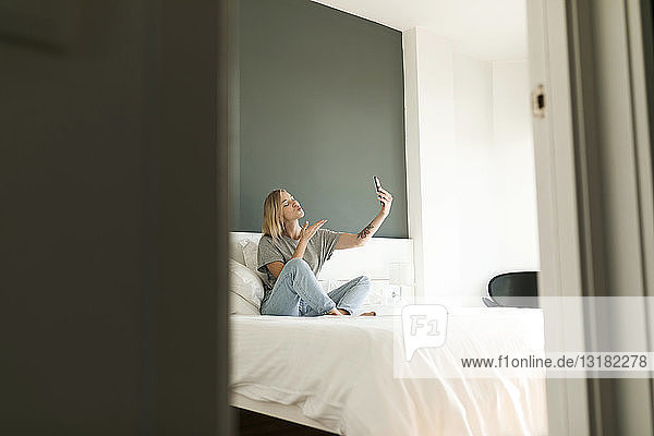 Young woman sitting on bed taking a selfie