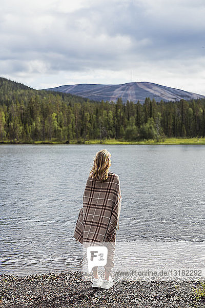 Finland  Lapland  woman wrapped in a blanket standing at the lakeside