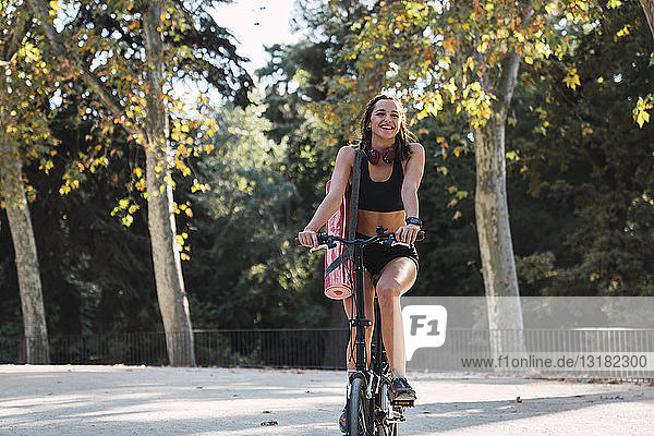 Fit young woman carrying yoga mat  riding bicycle