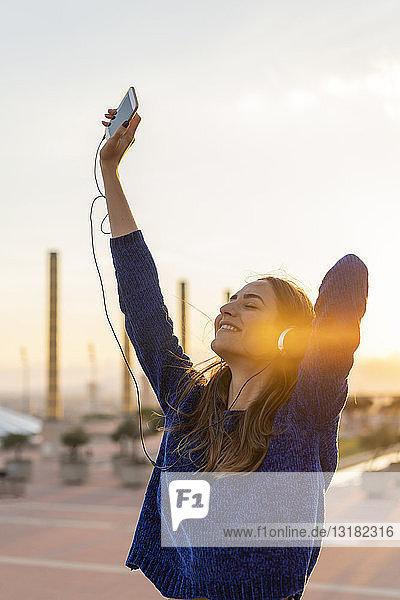 Spanien  Barcelona  Montjuic  glückliche junge Frau  die bei Sonnenuntergang mit Kopfhörern Musik hört