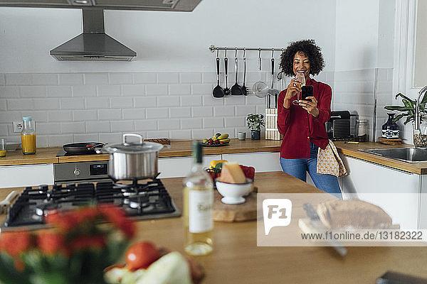 Woman standing in her kitchen  taking a selfie  drinking wine