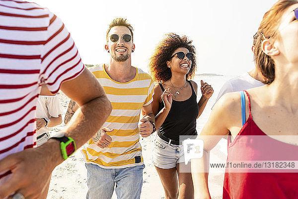 Freunde amüsieren sich gemeinsam  laufen am Strand