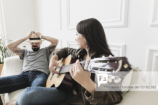 Relaxed couple sitting on couch  woman playing the guitar at home