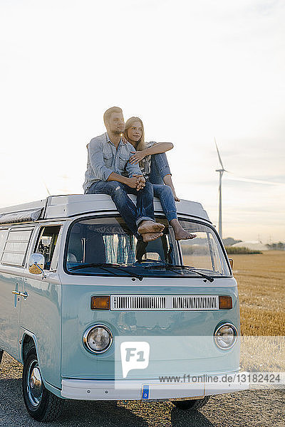 Affectionate young couple on roof of a camper van in rural landscape