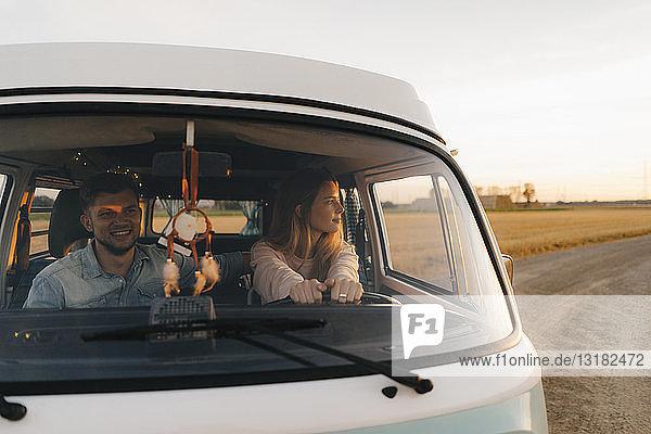 Ehepaar fährt Wohnmobil auf Feldweg in ländlicher Landschaft