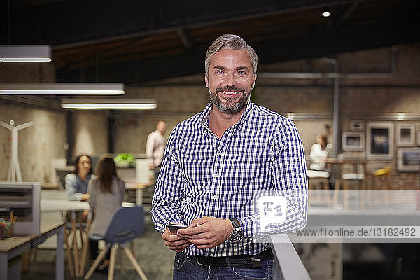 Businessman standing in office holding smartphone