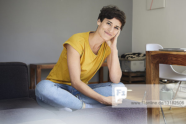 Portrait of smiling woman sitting on couch at home