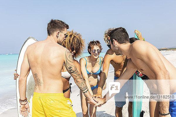 Gruppe von Freunden am Strand beim Händestapeln