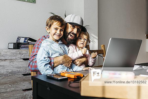 Vater arbeitet zu Hause und benutzt einen Laptop mit seinen Kindern auf dem Schoß
