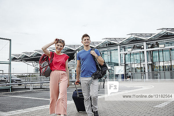 Lächelndes Paar zu Fuß vor dem Flughafen