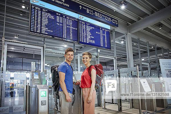 Porträt eines lächelnden Paares am Sicherheitstor am Flughafen
