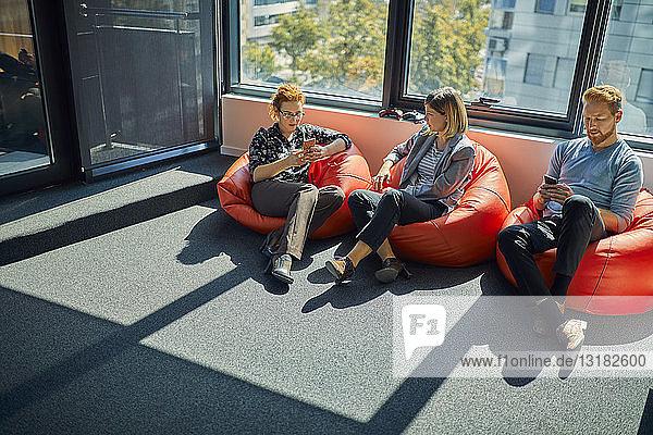 Kollegen mit Mobiltelefonen sitzen in Sitzsäcken in der Büro-Lounge