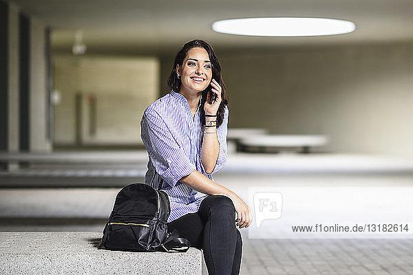 Porträt eines lächelnden Studenten am Telefon