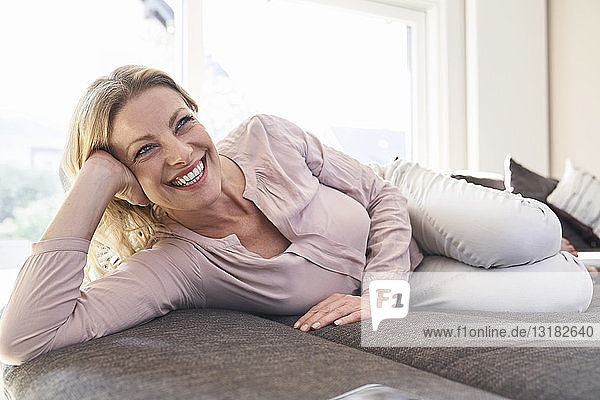 Happy woman lying on couch at home