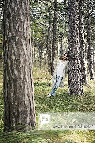 Gelassene Frau steht im Wald