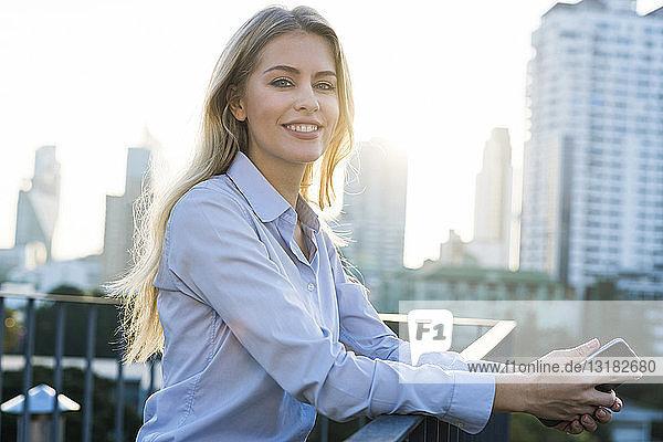 Blonde lächelnde Geschäftsfrau lehnt am Handlauf und hält ein Smartphone auf dem Dach der Stadt
