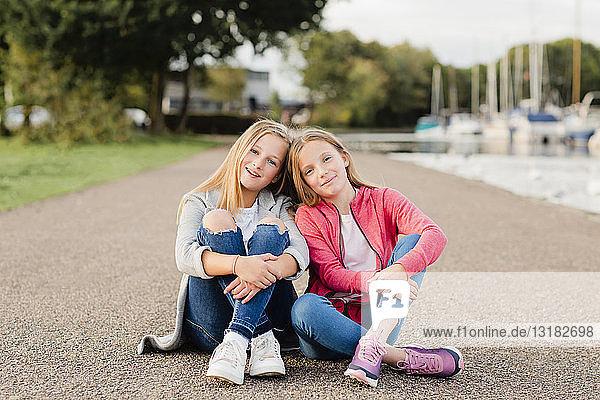 Porträt von zwei lächelnden Mädchen  die Kopf an Kopf auf dem Boden sitzen