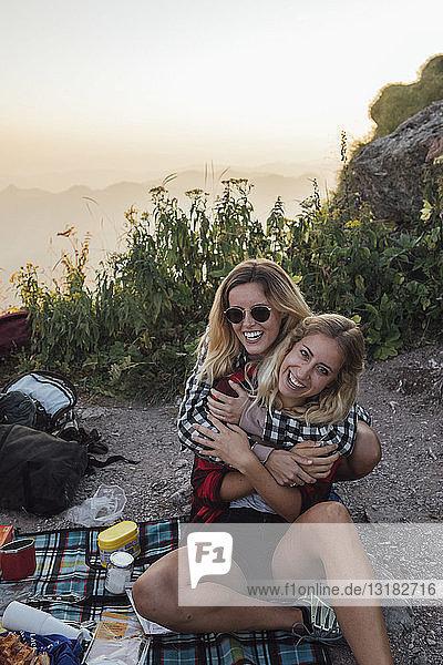 Schweiz  Grosser Mythos  zwei glückliche Freundinnen auf Wanderung mit Picknickpause bei Sonnenaufgang Schweiz, Grosser Mythos, zwei glückliche Freundinnen auf Wanderung mit Picknickpause bei Sonnenaufgang