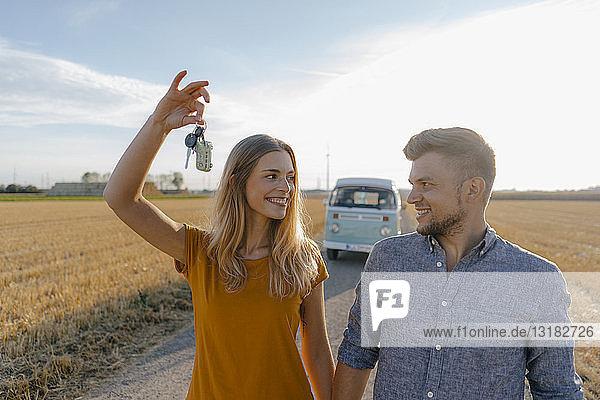 Junges Paar mit Autoschlüssel auf Feldweg am Wohnmobil in ländlicher Landschaft