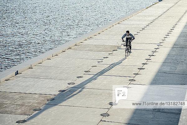Junger Mann fährt Fahrrad auf der Uferpromenade am Flussufer