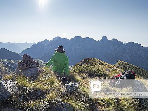 Italien  Lombardei  Bergamaskische Voralpen  Wanderer sitzt auf dem Aussichtspunkt des Monte Gardena  Cima Bagozza gegen die Sonne