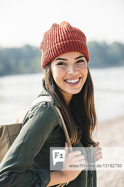 Porträt einer lächelnden jungen Frau am Flussufer