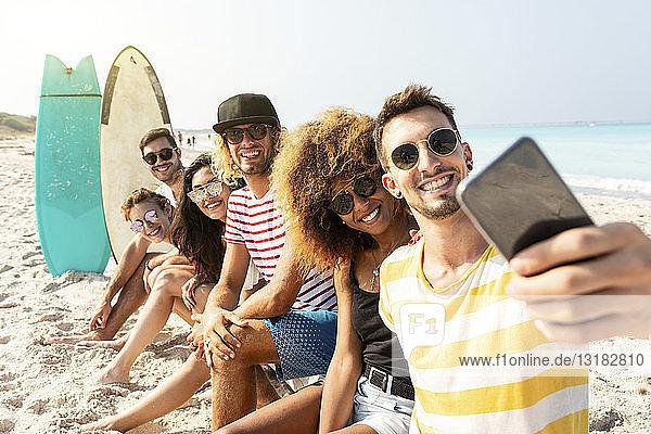 Freunde sitzen am Strand  haben Spaß  nehmen sich selbst