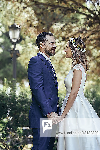 Happy bridal couple standing face to face in a park holding hands