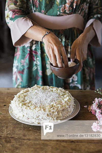 Young woman garnishing home-baked cake  partial view