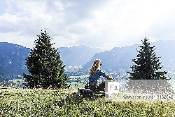 Deutschland  Bayern  Oberammergau  junge Frau wandert auf Bank sitzend auf Bergwiese