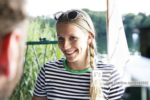 Young woman smiling at man at a lake next to sailing boat
