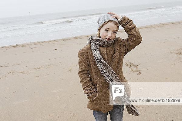 Porträt eines Jungen  der im Winter am Strand steht