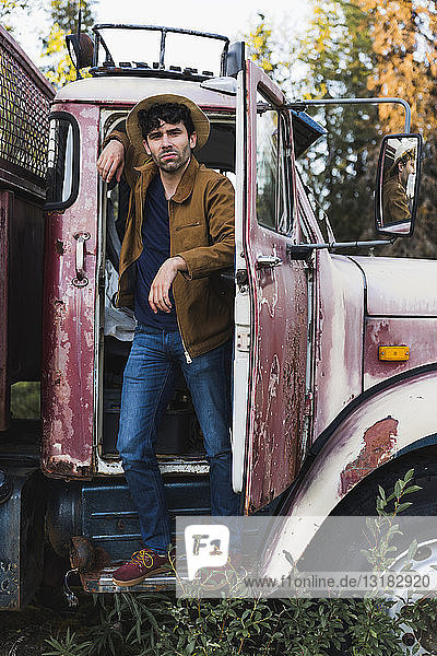 Cool young man standing in cabin of a broken truck
