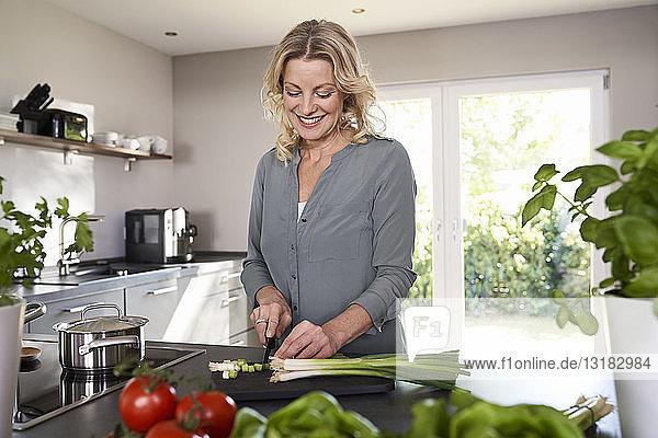 Lächelnde Frau schneidet Frühlingszwiebeln in der Küche