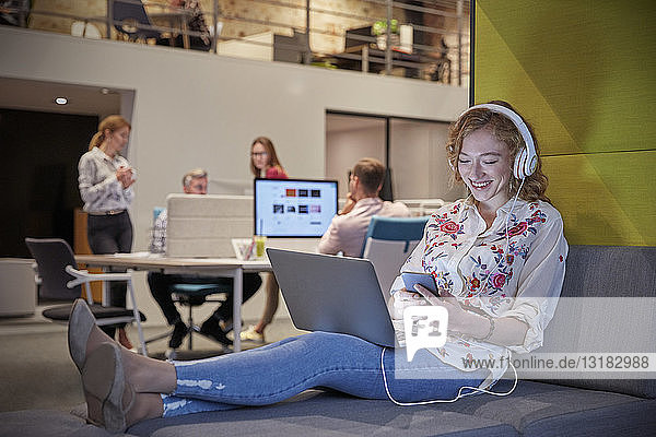 Young woman working in modern creative office  usine laptop and headphones