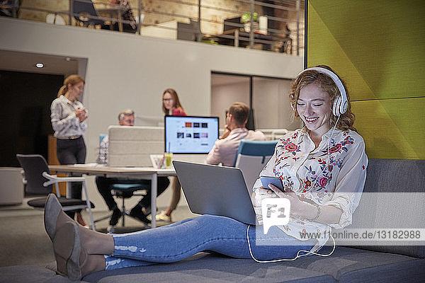 Junge Frau  die in einem modernen Kreativbüro arbeitet  benutzt Laptop und Kopfhörer