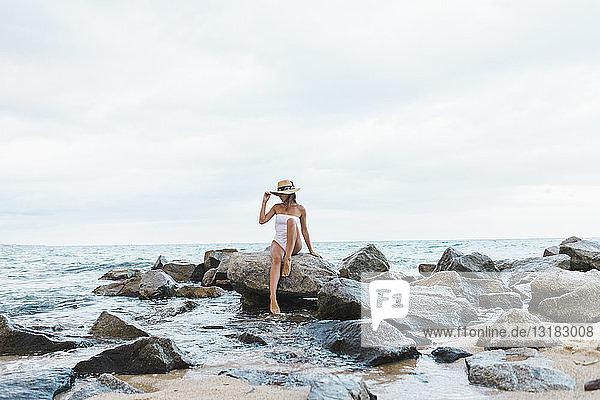 Junge Frau im Badeanzug und mit Hut auf einem Felsen im Meer sitzend